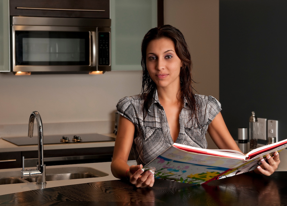 Young hispanic woman reading a book in a modern apartment.