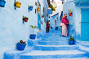 CHEFCHAOUEN, MOROCCO - 28th MARCH 2014 - Locals to Chefchaouen walk through a colourful street and steps lined with decorative flower and plant pots, Chefchaouen - the blue city - Rif Mountains, Northern Morocco.