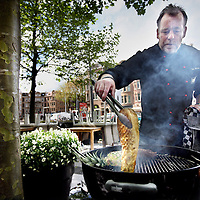 Nederland, Amsterdam , 23 mei 2013.<br /> Topkok Ron Blaauw tijdens barbecuen van long beef en kool buiten op het terras van zijn restaurant aan de Amstelveenseweg.<br /> Ron Blaauw is een  Nederlands chef-kok en televisiepersoonlijkheid. Hij gaf zijn 2 michelinssterren op.<br /> TV-chef and top chef Ron Blaauw barbequeing beef and cabbage on the terrace of his restaurant. He gave up his 2 Michelin stars in order to stay cool and normal.