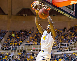 West Virginia Mountaineers guard Daxter Miles Jr. (4) dunks the ball on a break away against the Texas Longhorns during the second half at the WVU Coliseum.