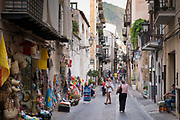 Street scene and souvenir shops in coastal town of Cefalu with Baroque style architecture in Northern Sicily, Italy