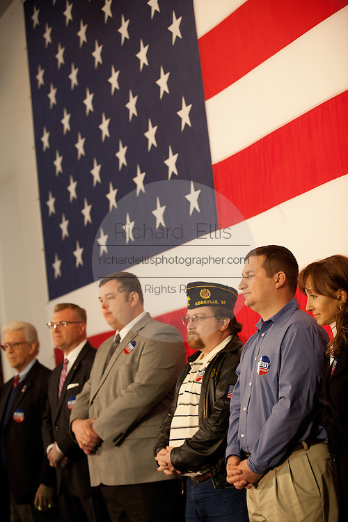 US military veterans stand in front of a giant American flag as they wait to hear Republican presidential candidate Gov. Rick Perry aboard the USS Yorktown museum on December 8, 2011 in Mt Pleasant, South Carolina.
