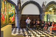 Belgie, Brugge, 20150529.<br /> Studenten kunstgeschiedenis luisteren naar de uitleg van de docent in het Memling in Sint-Jan museum. Ze kijken naar het Het Johannesretabel. Een triptiek rond Johannes de Doper.Het Memling in Sint-Jan museum is gesitueerd in het Oud Sint-Janshospitaal in het centrum van Brugge.Belgie, Brugge, 20150529Art history students listen to the explanation of the teacher in the Memling Museum in Saint John. They look at John's Altarpiece. A triptych about John the BaptistThe Memling Museum in Saint John is located in Old St. John's Hospital in the center of Bruges.Summer Course 2015 Emerson College