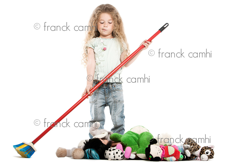 caucasian little girl sweeping toys isolated studio on white background