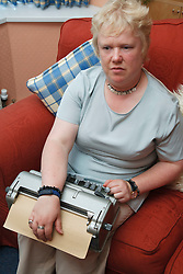 Woman with visual impairment at home reading braille on braille typewriter.