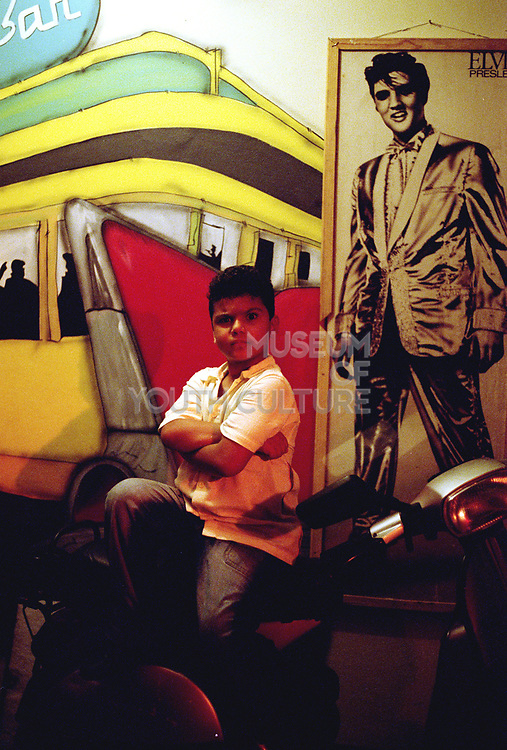 Boy posing for the camera next to a picture of Elvis, Brazil, 2000's
