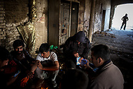 Migrants warming up next to a bone fire in an abandoned brick factory in Subotica few kilometers from the Hungarian border. Migrants are still trying to cross even after the Hungarian police reinforced their personel on the border. migrants pays abourt 1500 euros to smiugglers to try to cross, but the chanches are very fews. March 17th, 2017, Belgrade, Serbia. Federico Scoppa/CAPTA