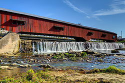 2015 Oct 19:   Parke County Indiana is the site of the Indiana Covered Bridge Festival every October.  This is the Bridgeton.  It was built over Big Raccoon Creek in Bridgeton in 2006 to replace an original bridge which was destroyed by arson in 2005.  It was completely rebuilt private funds. The bridge has a 245' span.  The original bridge was built in 1868 by J.J. Daniels and was 261' in length.<br /> <br /> Bridgeton Mill is thought to be the 2nd oldest continuously private operated mill in the United States.  The mill was built 1823 and rebuilt in 1870.  The mills foundation is actually part of the dam, the water fall is 200' wide.  The mill currently offers cornbread, pancake miss and other 100% stone ground products.<br /> <br /> This image was produced in part utilizing High Dynamic Range (HDR) processes.  It should not be used editorially without being listed as an illustration or with a disclaimer.  It may or may not be an accurate representation of the scene as originally photographed and the finished image is the creation of the photographer.