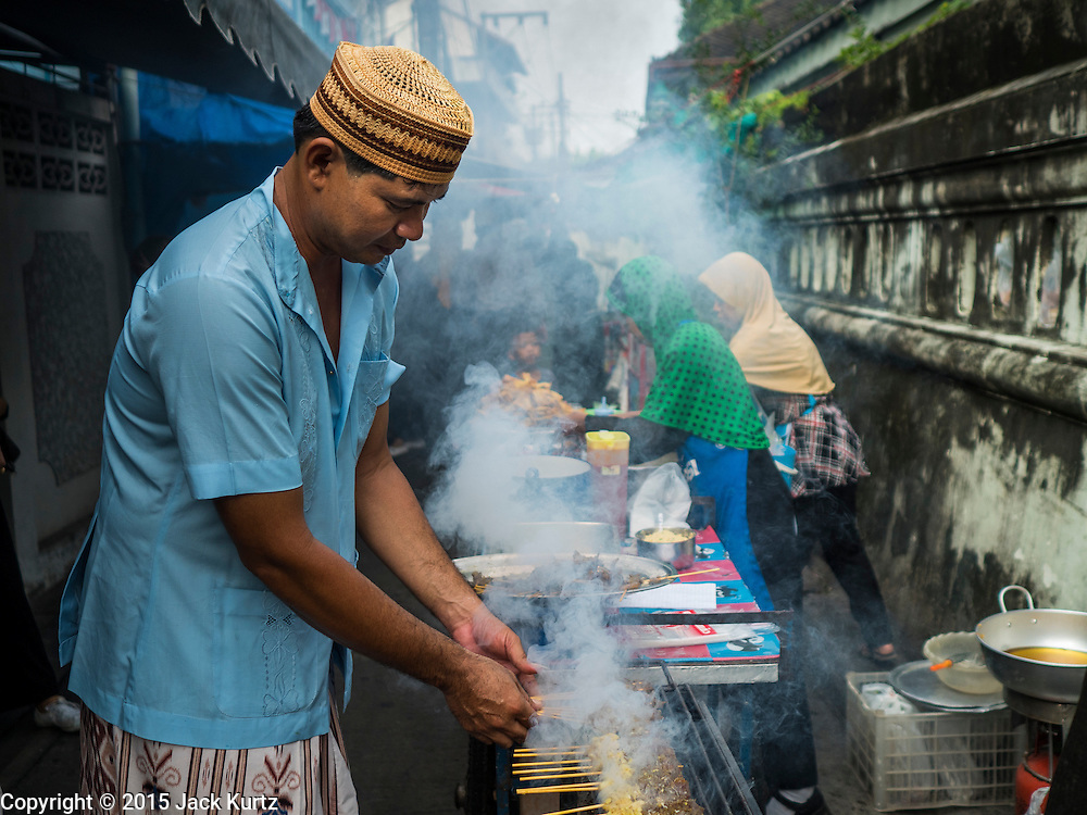 17 JULY 2015 - BANGKOK, THAILAND:     A street food vendor near Ton Son Mosque in Bangkok grills chicken for Muslims celebrating Eid al-Fitr. Eid al-Fitr is also called Feast of Breaking the Fast, the Sugar Feast, Bayram (Bajram), the Sweet Festival or Hari Raya Puasa and the Lesser Eid. It is an important Muslim religious holiday that marks the end of Ramadan, the Islamic holy month of fasting. Muslims are not allowed to fast on Eid. The holiday celebrates the conclusion of the 29 or 30 days of dawn-to-sunset fasting Muslims do during the month of Ramadan. Islam is the second largest religion in Thailand. Government sources say about 5% of Thais are Muslim, many in the Muslim community say the number is closer to 10%.          PHOTO BY JACK KURTZ