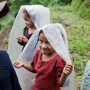 Children in the rice fields with their parents shielding themselves from the rain.
