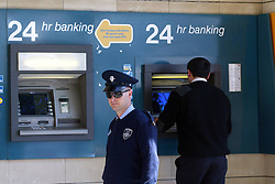 A policeman stands near an ATM outside a branch of Laiki Bank in Nicosia, capital of Cyprus, on March 28, 2013. Surprisingly few lined up outside banks in Cyprus when they reopened for business at noon on Thursday -- to the relief of authorities which have feared a run on the banks following a closure since March 16. Strict limits on bank transactions have been announced by the Central Bank and the ministry of finance in a bid to prevent a massive outflow of cash. A Central Bank official said banks would be open for transactions between 12:00 noon and 18:00 local time (10:00 GMT and 16:00 GMT), instead of the normal 08:30 to 13:00 local time bank hours. The decree imposing controls on bank transaction limits cash withdrawal to 300 euros per day per bank account and entirely prohibits payment by check. However, credit card holders can use them for commercial transactions for unlimited amounts of money, Nicosia, Cyprus, March 28, 2013. Photo by Imago / i-Images...UK ONLY.