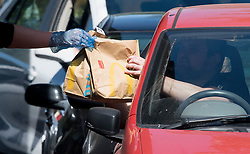 © Licensed to London News Pictures. 20/05/2020. Staines, UK. A McDonalds employee hands food to a customer at a McDonalds Drive Thru in Staines, Surrey. Branches of McDonalds restaurants have opened for drive thru today for the fist time since lockdown.  todayGovernment has announced a series of measures to slowly ease lockdown, which was introduced to fight the spread of the COVID-19 strain of coronavirus. Photo credit: Ben Cawthra/LNP
