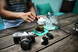 A man stirs his iced coffee in a coffee shop of Hoi An, Vietnam, Southeast Asia