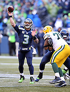 Seattle Seahawks quarterback Russell Wilson (3) throws a late fourth quarter pass to Seattle Seahawks running back Marshawn Lynch (24) for a touchdown that gets reviewed and reversed to a first and goal at the Green Bay Packers 9 yard line during the NFL week 20 NFC Championship football game against the Green Bay Packers on Sunday, Jan. 18, 2015 in Seattle. The Seahawks won the game 28-22 in overtime. ©Paul Anthony Spinelli