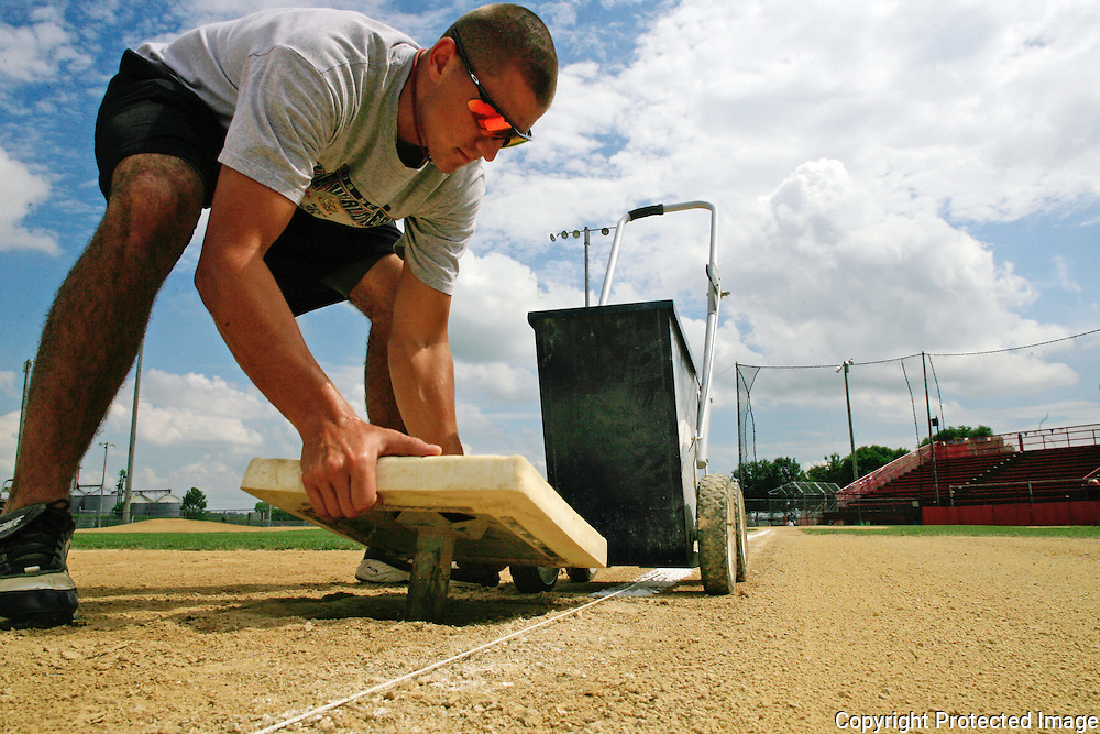 DOUBLE DUTY - Clarinda A's infielder Ryan Bilovesky helped chalk the field and set the bases prior to a home game in July.  photo by David Peterson