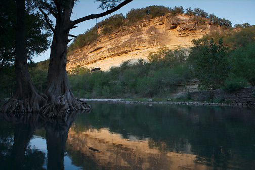 Stock photo of a cliff reflected in the river in the Texas Hill Country