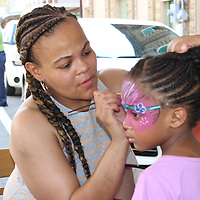 Carrness Gleghorn of Hattiesburg paints Kinsley Gleghorn's face at one of the several vendor booths.