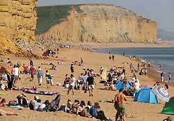 © Licensed to London News Pictures. 20/04/2019. West Bay, UK.  Member son the public enjoy the warm weather  at West Bay Beach on Dorset, south west England. The UK could experiencing record temperatures for an Easter Bank Holiday weekend.  Photo credit: Jason Bryant/LNP