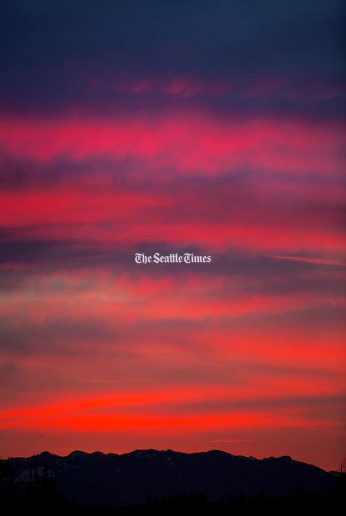 A winter sunrise over the Cascade Mountain range lights up the cloudy skies in this view from the Horizon View neighborhood of Lake Forest Park on Thursday morning. (Mike Siegel / The Seattle Times)