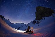 A snowmobile in the Swiss Alps, on a starry night.