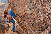 Professional climber Beth Rodden bouldering at the Buttermilk Boulders near Bishop California, USA.