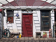 An odd small building with a bright red door in the SoHo neighborhood of Manhattan with junk littered around the exterior.  There are a series of rails erected that cast shadows accross and down the front of the white brick front.