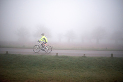 © Licensed to London News Pictures. 13/03/2014. Richmond, UK. A cyclist makes his way through the fog. Deer graze and feed in the heavy fog at Richmond Park, Surrey, today 13th March 2014. Photo credit : Stephen Simpson/LNP