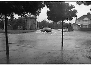 "Flooding at the Dodder..1986..26.08.1986..08.26.1986..28th August 1986..As a result of Hurricane Charly (Charlie) heavy overnight rainfall was the cause of severe flooding in the Donnybrook/Ballsbridge areas of Dublin. In a period of just 12 hours it was stated that 8 inches of rain had fallen. The Dodder,long regarded as a ""Flashy"" river, burst its banks and caused great hardship to families in the 300 or so homes which were flooded. Council workers and the Fire Brigades did their best to try and alleviate some of the problems by removing debris and pumping out some of the homes affected..Note: ""Flashy"" is a term given to a river which is prone to flooding as a result of heavy or sustained rainfall...A motorist manages to get through the worst of the flood water at the junction."