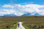 Tourists cycling by Stac Pollaidh - Stack Polly - (centre) in glacier mountain range in the North West Highlands Geopark in Coigach region of Scottish Highlands