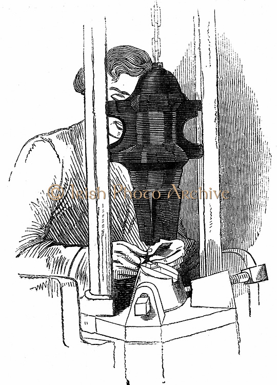 Die-stamping the channel and eye position on needle wires, Redditch, England. Foot-operated 13.6kg hammer. Woodcut c1835