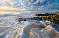Stunning cloud formations and breathtaking early light, highlight the seaweed decorated rocks jutting out into the white surf of Yaroomba.