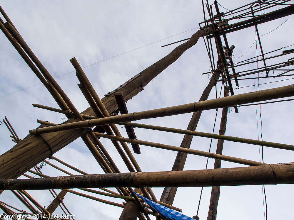 17 SEPTEMBER 2014 - SANGKHLA BURI, KANCHANABURI, THAILAND: A Thai soldier works at the top of a piling on the Mon Bridge in Sangkhla Buri. The 2800 foot long (850 meters) Saphan Mon (Mon Bridge) spans the Song Kalia River. It is reportedly second longest wooden bridge in the world. The bridge was severely damaged during heavy rainfall in July 2013 when its 230 foot middle section  (70 meters) collapsed during flooding. Officially known as Uttamanusorn Bridge, the bridge has been used by people in Sangkhla Buri (also known as Sangkhlaburi) for 20 years. The bridge was was conceived by Luang Pho Uttama, the late abbot of of Wat Wang Wiwekaram, and was built by hand by Mon refugees from Myanmar (then Burma). The wooden bridge is one of the leading tourist attractions in Kanchanaburi province. The loss of the bridge has hurt the economy of the Mon community opposite Sangkhla Buri. The repair has taken far longer than expected. Thai Prime Minister General Prayuth Chan-ocha ordered an engineer unit of the Royal Thai Army to help the local Mon population repair the bridge. Local people said they hope the bridge is repaired by the end November, which is when the tourist season starts.    PHOTO BY JACK KURTZ