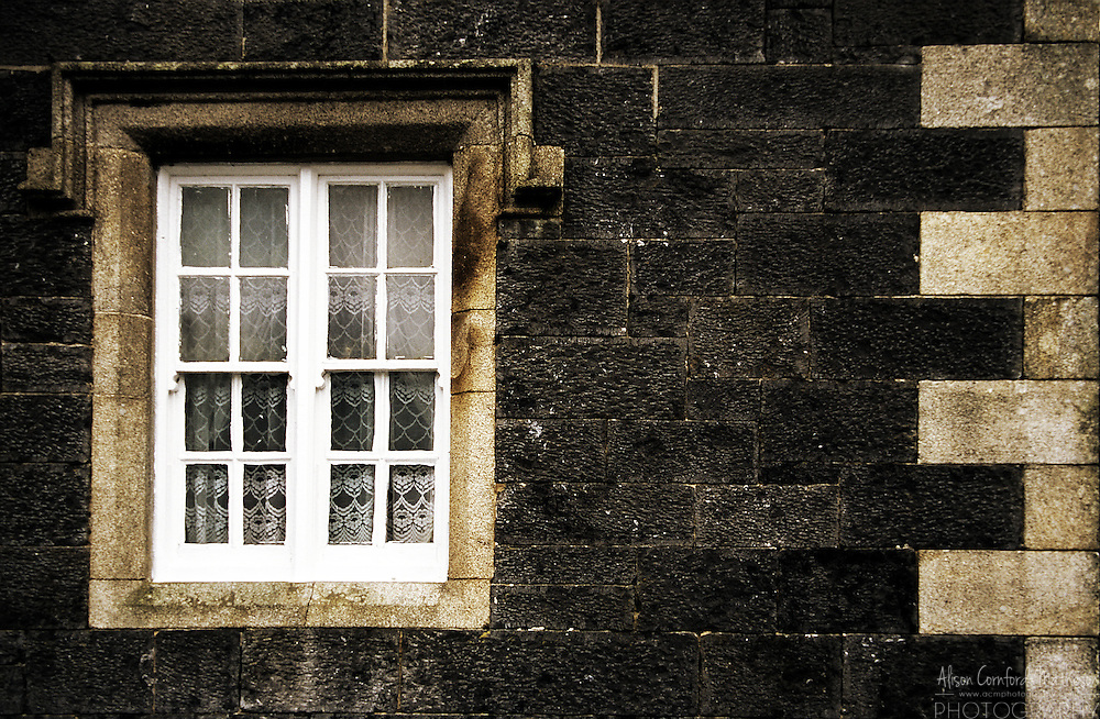 Window with lace curtains at a train station in rural Ireland