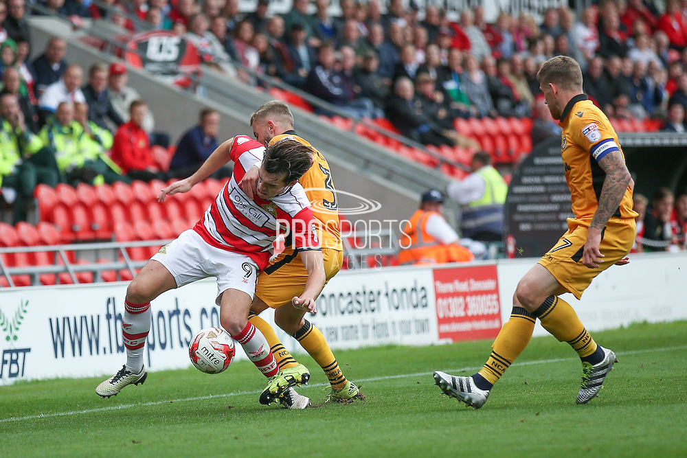 Doncaster Rovers forward John Marquis (9)  is fouled by Newport County  defender Dan Butler (3)  during the EFL Sky Bet League 2 match between Doncaster Rovers and Newport County at the Keepmoat Stadium, Doncaster, England on 17 September 2016. Photo by Simon Davies.
