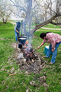 Henry Real Bird, Crow Indian, poet, author, stirs potatoes, helping daughter Lucy cook at her graduation celebration, Crow Indian Reservation, Montana