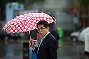 Passanten mit einem bunten Regenschirm schuetzen sich gegen den Regen in der Naehe des Express Bus Terminals im Zentrum der koreanischen Hauptstadt Seoul.<br /> <br /> Passersby protecting themselves with a colorful umbrealla against the rain close to the Express Bus Terminal in the city center of the Korean capital Seoul.