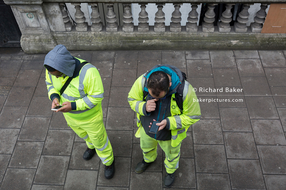 Two workmen take a break from a nearby construction site to use their mobile phones, on 8th April 2019, in London, England