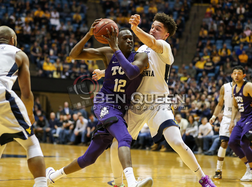 Feb 12, 2018; Morgantown, WV, USA; TCU Horned Frogs forward Kouat Noi (12) drives against West Virginia Mountaineers forward Teddy Allen (13) during the first half at WVU Coliseum. Mandatory Credit: Ben Queen-USA TODAY Sports