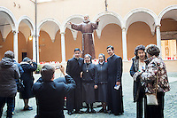 ROME, ITALY - 5 FEBRUARY 2016: Priests and nuns pose for a picture in front of a statue of Saint Pio in the cloister of the church of San Salvatore in Lauro, where the relics of Saint Pio and Saint Leopold are exposed,  in Rome, Italy, on February 5th 2016.<br /> <br /> Crowds of tens of thousands faithfuls and pilgrims greeted the arrival of the relics of Saint Pius of Pietrelcina – better known as Padre Pio – and Saint Leopold Mandic in Rome. On the afternoon of February 5h, the two saint will be taken in procession to St-Peter's basilica.<br /> <br /> Saint Pio and Saint Leopold were two Franciscans that lived in the 20th century and that are well known as confessors and spiritual guides. Pope Francis himself requested that the relics of the saints come to Rome, in part to inspire the ministry of the priests who have been chosen as Missionaries of Mercy for the Jubilee.