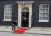 London News pictures. 01.03..2011. A maintainance worker brushes the red carpet outside Downing Street. British Prime Minister David Cameron meets Afghanastan's President Karzai today (3rd March 2011) in Downing Street, London. Picture Credit should read Stephen Simpson/LNP