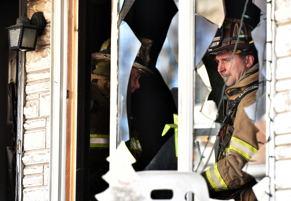 A firefighter is seen through the broken windows leaving the fire scene on Pulaski  street in Kingston as another enters.