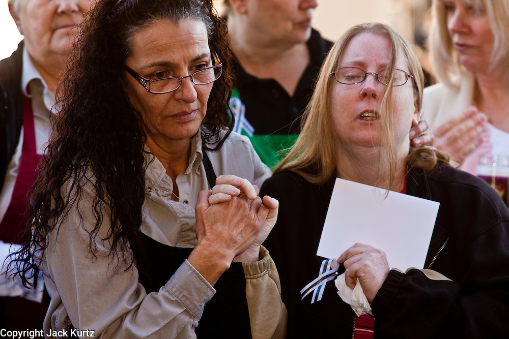 "15 JANUARY 2010 - TUCSON, AZ:    Safeway employees DAWN GALLAGHER (left, dark hair) comforts SHAYNE SPUDE (right) at the memorial for the victims of a a mass shooting in Tucson, AZ, Saturday, January 15, one week after the shooting. Six people were killed and 14 injured in the shooting spree at a ""Congress on Your Corner"" event hosted by Arizona Congresswoman Gabrielle Giffords at a Safeway grocery store in north Tucson on January 8. Congresswoman Giffords, the intended target of the attack, was shot in the head and seriously injured in the attack but is recovering. Doctors announced that they removed her breathing tube Saturday, one week after the attack. The alleged gunman, Jared Lee Loughner, was wrestled to the ground by bystanders when he stopped shooting to reload the Glock 19 semi-automatic pistol. Loughner is currently in federal custody at a medium security prison near Phoenix.  PHOTO BY JACK KURTZ"