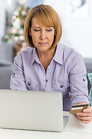 Mature woman shopping online at home during Christmas