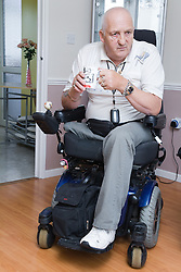 Male wheelchair user having a cup of tea;