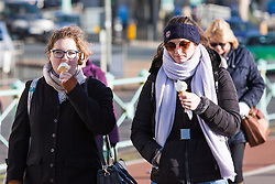 © Licensed to London News Pictures. 26/11/2017. Brighton, UK. Two women dressed in hats and scarfs eat an ice cream as cold weather is hitting Brighton and Hove. Photo credit: Hugo Michiels/LNP