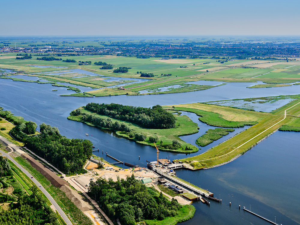 "Nederland, Overijssel, Gemeente Kampen; 21–06-2020; Reevesluis en monding van het Reevediep in het Revemeer (voorheen Drontermeer).<br /> Het Reevediep is aangelegd in het kader van het project Ruimte voor de Rivier om bij hoogwater water af te voeren voordat dit het nabij gelegen Kampen bereikt, direct naar het IJsselmeer, de 'bypass Kampen'. Het Reevediepgebied is ook een natuurgebied en vormt een ecologische verbindingszone tussen rivier de IJssel en Drontermeer.<br /> Mouth of the Reevediep en Reeve lock.<br /> The Reevediep has been constructed as part of the Room for the River project, and functions to discharge high waters before reaching the nearby Kampen, directly to the IJsselmeer, the ""bypass Kampen"". The Reevediep area is also a nature reserve and forms an ecological connecting zone between the river IJssel and Drontermeer.<br /> <br /> luchtfoto (toeslag op standaard tarieven);<br /> aerial photo (additional fee required)<br /> copyright © 2020 foto/photo Siebe Swart"