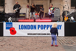 Covent Garden, London, October 30th 2014. They Royal British Legion's Poppy Day in London centred around Covent Garden where bands, choirs, classical and pop musicians entertained crowds as Air Force personnel carrying donation buckets sold poppies, hoping to raise in excess of £1 million. Pictured: Rock band Mixtape Nation performs as two-year-old Sylvia Taunt dances in front of the stage.