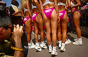 During the Cannes Film Festival, a group of girls from the Hawaiian Tropic sun cream company pose in bikinis and reveal swimwear for a frenzy of males of various ages on La Croisette, Cannes sea front in the French Riviera resort, Cote d'Azur. They pose in the same corporate style for photographers around the world but here, young women publicising movies or just themselves, regularly strut along the beaches and pavements of this French town. The weather is typically bright for May with clear skies and high temperatures. Cannes  is a major tourist centre and a leading resort on the French Riviera. Located in the Alpes-Maritimes région, Founded in 1939, the International Film Festival is one of the world's most prestigious and eccentric of celebrations of film and the cinema industry.