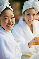 Two young women wearing bathrobes at health spa, portrait