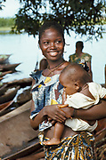Portrait of smiling woman carrying baby along Ngiri River, Democratic Republic of the Congo (ex-Zaire), Africa.